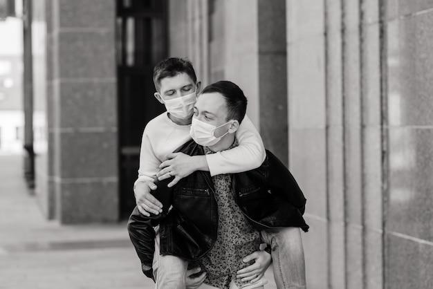 Junges schwules paar, das medizinische maske trägt, die stadt umarmt und küsst
