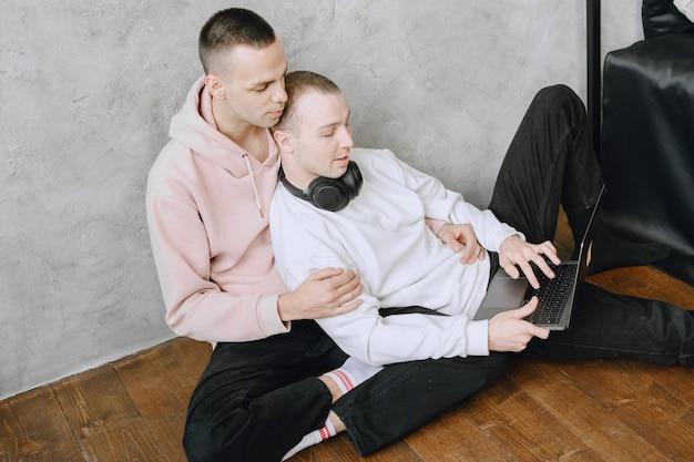 Junges schwules paar, das mit laptop auf dem boden sitzt, mit kopfhörern zusammen musik hört, sich umarmt