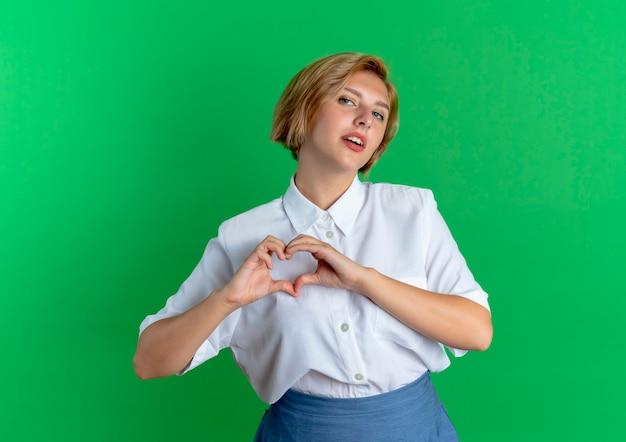 Junges selbstbewusstes blondes russisches mädchen gestikuliert herzhandzeichen