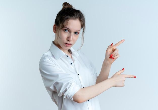 Junges selbstbewusstes blondes russisches mädchen zeigt zur seite mit zwei fingern, die auf weißem raum mit kopienraum lokalisiert werden