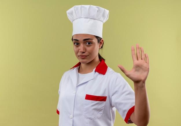 Junges selbstbewusstes kaukasisches kochmädchen in den einheitlichen gesten des küchenchefs stoppen handzeichen lokalisiert auf grüner wand mit kopienraum