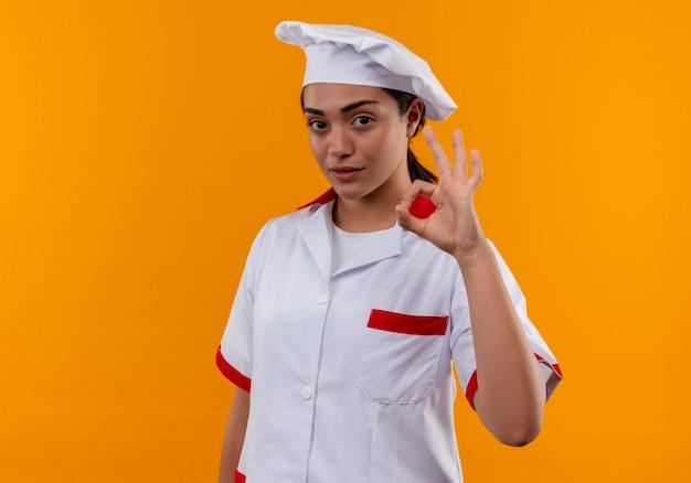 Junges selbstbewusstes kaukasisches kochmädchen in der kochuniform gestikuliert ok handzeichen lokalisiert auf orange wand mit kopienraum