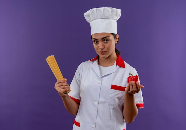 Junges selbstbewusstes kaukasisches kochmädchen in der kochuniform hält bündel von spaghetti und rotem pfeffer lokalisiert auf violetter wand mit kopienraum