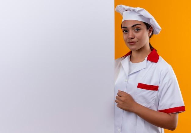 Junges selbstbewusstes kaukasisches kochmädchen in der kochuniform steht hinter weißer wand und hält faust isoliert auf orange wand mit kopienraum