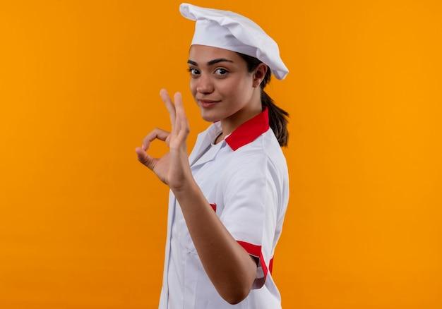 Junges selbstbewusstes kaukasisches kochmädchen in der kochuniform steht seitlich und gestikuliert ok handzeichen lokalisiert auf orange wand mit kopienraum