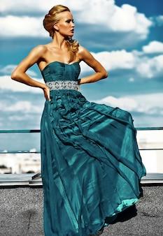 Junges sexy blondes frauenmodell im abendkleid, das auf hintergrund des blauen himmels aufwirft