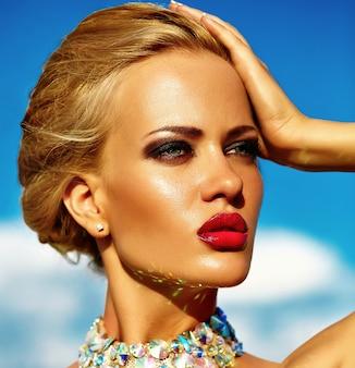 Junges sexy blondes frauenmodell, wenn das gelbe kleid geglättet wird, das auf hintergrund des blauen himmels aufwirft