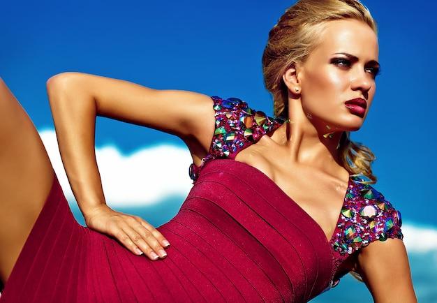 Junges sexy blondes frauenmodell, wenn das rote kleid geglättet wird, das auf hintergrund des blauen himmels aufwirft