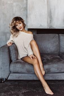 Junges sexy blondes mädchen, das auf dem sofa in einer strickjacke sitzt