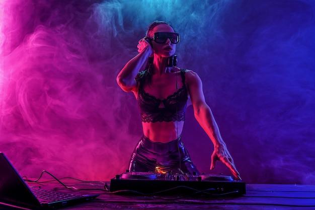 Junges sexy dj mit der sonnenbrille, die musik spielt