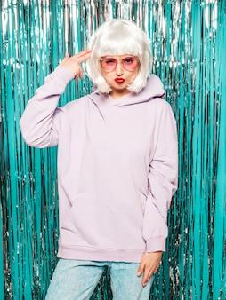 Junges sexy lächelndes hipster-mädchen in der weißen perücke und in den roten lippen. schöne trendige frau in der sommerkleidung. verärgertes modell, das auf blauem silbernem glänzendem lametta-hintergrund im studio aufwirft. weibliche nachahmende waffe