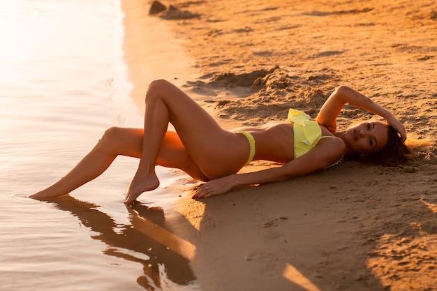 Junges sexy mädchen bei sonnenuntergang am strand