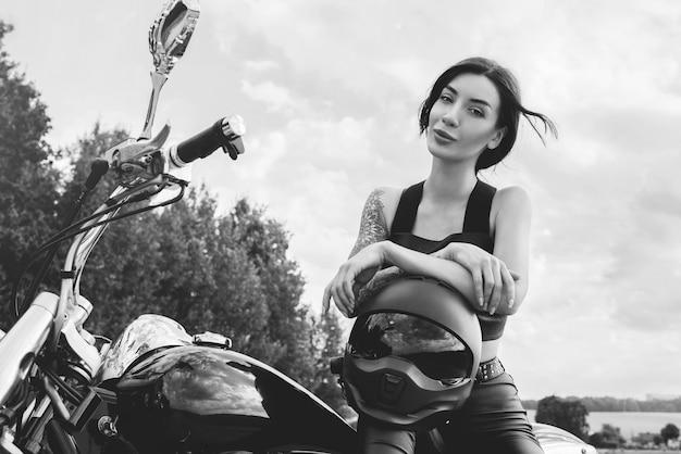 Junges sexy mädchen, das bei sonnenuntergang auf einem motorrad aufwirft. motorsportkonzept. gemischte medien