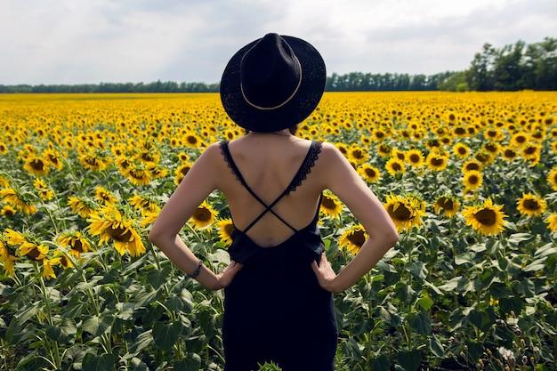 Junges sexy mädchen im schwarzen kleid und im hut im feld mit gelben sonnenblumen