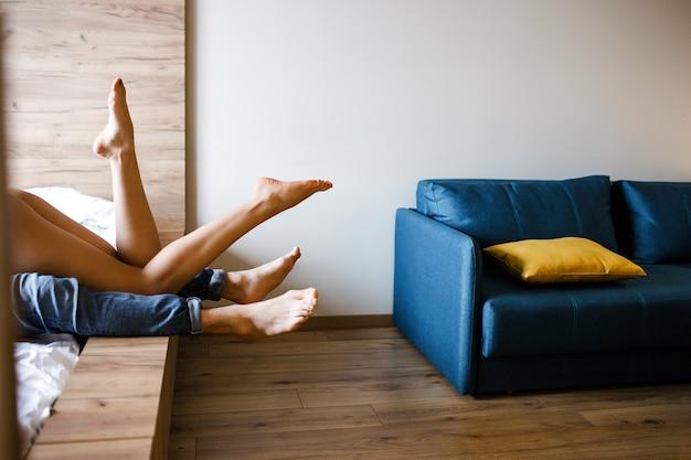 Junges sexy paar hat intimität auf dem bett. frau, die auf mann liegt. beine posieren vor der kamera. intimitätsprozess. vergnügen. liebe und lust. leidenschaftliches paar zusammen im zimmer