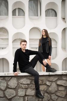 Junges sexy paar in schwarzer kleidung posiert mit einem hintergrund an der weißen wand
