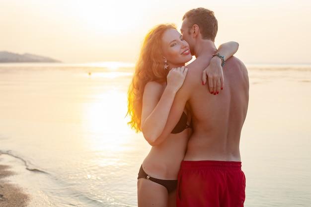 Junges sexy romantisches paar in der liebe glücklich am sommerstrand zusammen mit spaß, badeanzüge tragend