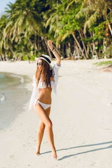 Junges sexy schlankes mädchen tanzt auf einem strand, der weiße bikini-badebekleidung trägt. sie trägt ein weißes hemd, eine dunkle sonnenbrille und einen strohhut. sie ist gebräunt und stilvoll.