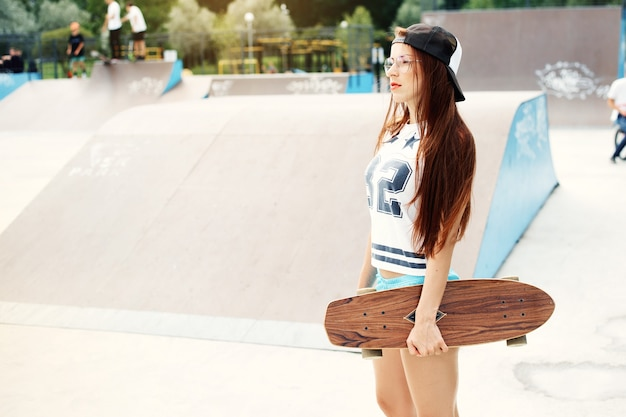Junges sexy schönes schlankes mädchen, das mit skateboard in der stadt geht. modischer mädchen-hipster in einer kappe und in einer sonnenbrille.