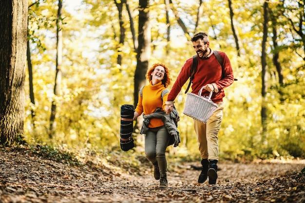 Junges spielerisches lächelndes glückliches paar in der liebe, die hände hält und in der natur an einem schönen herbsttag läuft. paar hält picknickausrüstung.