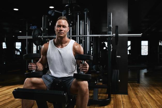 Junges sportathleten-fitness-modell in der turnhalle schüttelt seinen bizeps mit hanteln. sportliche motivation, zurückhaltend, hoher kontrast. das konzept eines gesunden lebensstils, lebensbewegung, kopienraum.