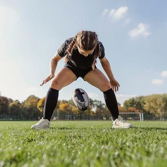 Junges sportives mädchen, das einen rugbyball fallenläßt