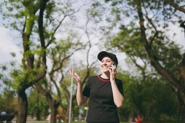 Junges sportlich lächelndes schönes brünettes mädchen in schwarzer uniform und mütze, das während des trainings mit dem handy spricht, beiseite schaut und im stadtpark im freien steht