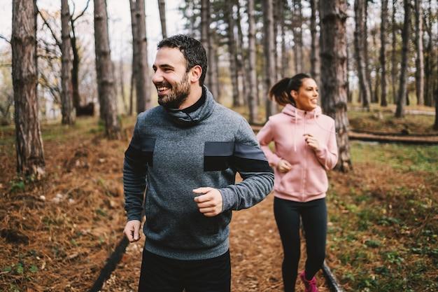 Junges sportliches fröhliches paar, das im wald läuft und sich auf marathon vorbereitet. mann ist schneller als frau und er gewinnt.