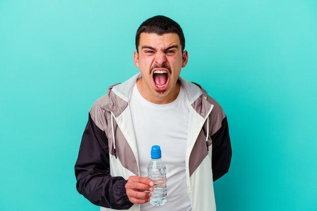 Junges sportliches kaukasisches manntrinkwasser isoliert auf blau, das sehr wütend und aggressiv schreit.