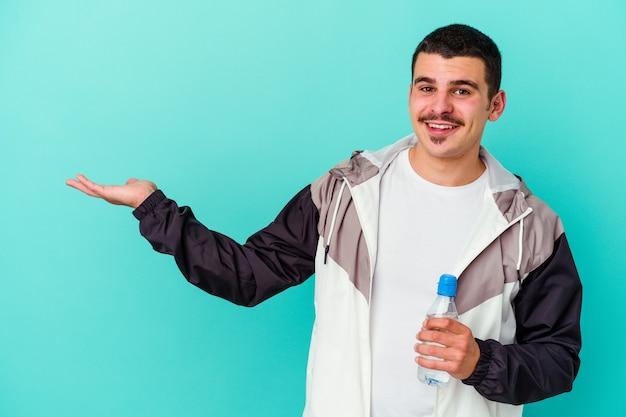 Junges sportliches kaukasisches manntrinkwasser lokalisiert auf blau, das einen kopienraum auf einer handfläche zeigt und eine andere hand auf taille hält.