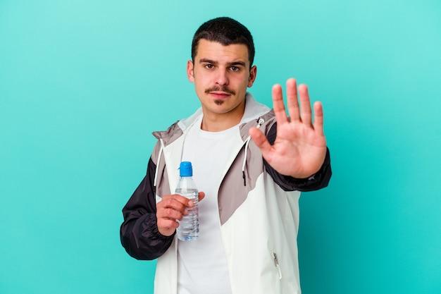 Junges sportliches kaukasisches manntrinkwasser lokalisiert auf blau stehend mit ausgestreckter hand, die stoppschild zeigt, das sie verhindert.