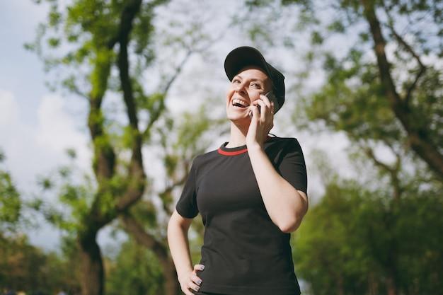 Junges sportliches lachendes schönes brünettes mädchen in schwarzer uniform und mütze, das während des trainings mit dem handy spricht, aufschaut und im stadtpark im freien steht standing