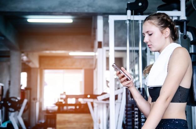 Junges sportliches mädchen, das nach einem intensiven training in der turnhalle mit dem smartphone hörend musik stillsteht