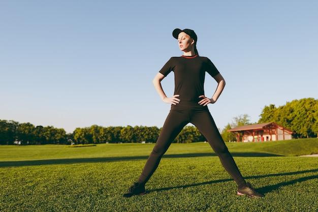 Junges sportliches mädchen in schwarzer uniform, mütze, die sportübungen macht, aufwärmübungen, dehnung vor dem laufen auf grünem rasen im golfplatzpark im freien an sonnigen sommertagen. fitness, gesundes lifestyle-konzept.