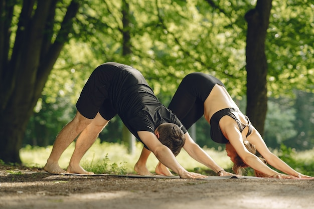 Junges sportliches paar, das yoga fitness tut. menschen in einem sommerpark.