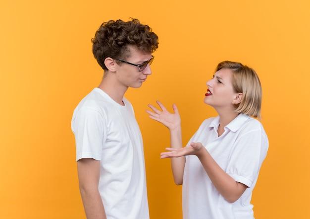 Junges sportliches paar mann und frau, die einander streitend und streitend betrachten, die über orange wand stehen