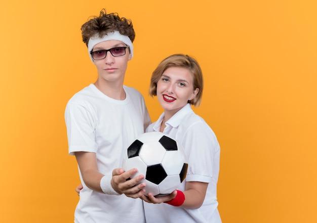 Junges sportliches paar mann und frau, die zusammenhalten fußball halten, der über orange wand lächelt