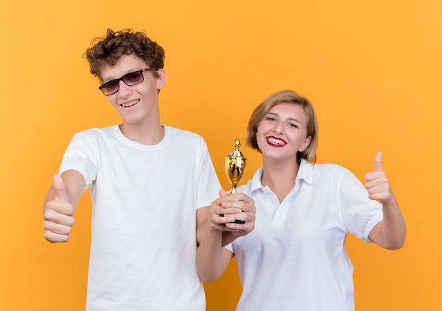 Junges sportliches paar mann und frau, die zusammenhalten trophäe zeigen daumen hoch lächelnd stehen über orange wand