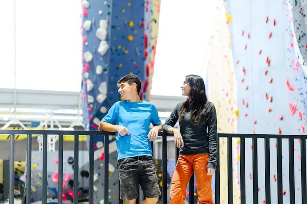 Junges sportliches wandkletterpaar, das künstliche kletterwand innen betrachtet