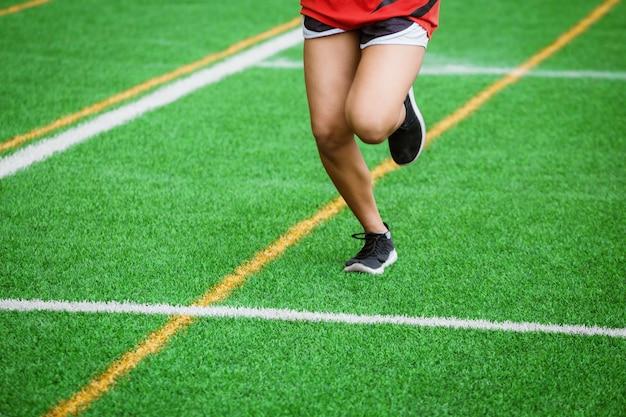 Junges sportmädchen, das auf sportfeld läuft