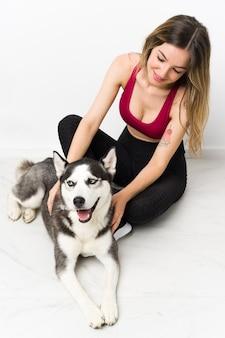Junges sportmädchen mit ihrem hund, der auf dem boden sitzt