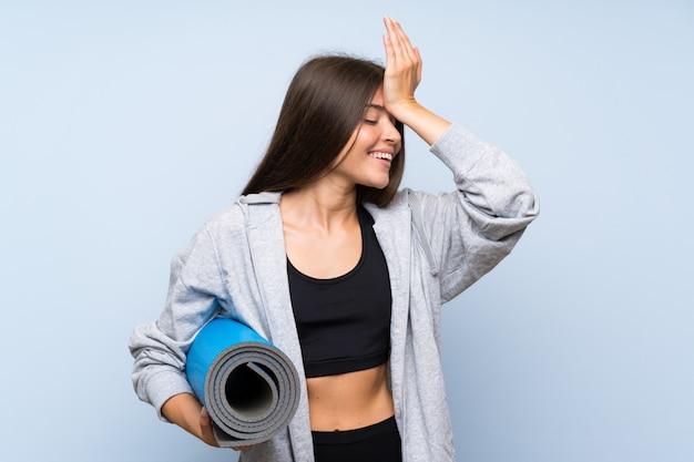 Junges sportmädchen mit matte über lokalisierter blauer wand hat etwas verwirklicht und die lösung beabsichtigt