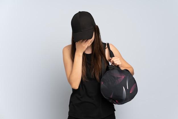 Junges sportmädchen mit sporttasche lokalisiert auf grau mit müde und krankem ausdruck