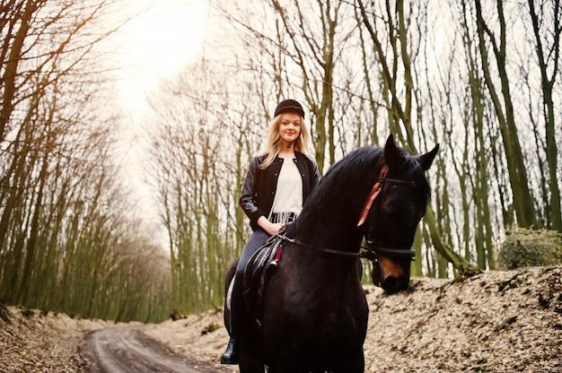 Junges stilvolles blondes mädchenreiten auf pferden am herbstwald