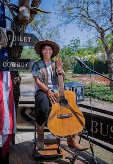 Junges stilvolles cowgirllächeln mit gitarre an der frühlingswiese im park.
