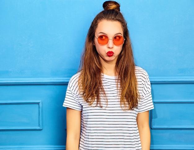 Junges stilvolles frauenmodell im zufälligen sommer kleidet mit den roten lippen und wirft nahe blauer wand auf. sie pustete auf die wangen