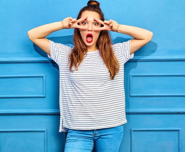 Junges stilvolles frauenmodell im zufälligen sommer kleidet mit den roten lippen und wirft nahe blauer wand auf. überrascht und zeigt friedenszeichen