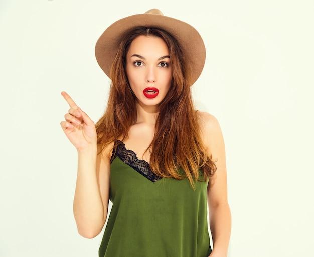 Junges stilvolles frauenmodell in der zufälligen sommergrünkleidung und im braunen hut mit den roten lippen kam die idee und sie legte ihren finger dar. isoliert