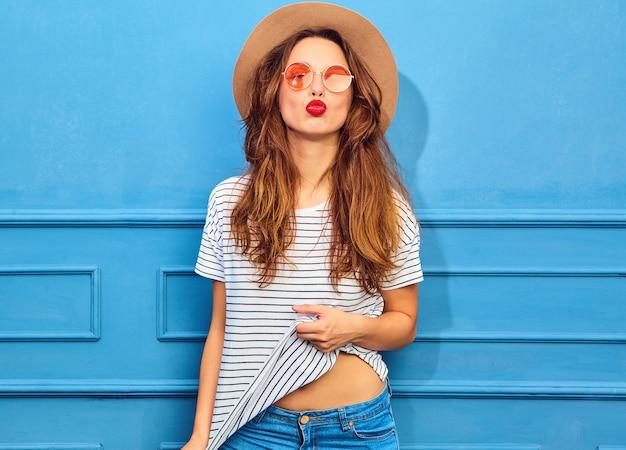 Junges stilvolles frauenmodell in der zufälligen sommerkleidung und im braunen hut mit den roten lippen, werfend nahe blauer wand auf. luft küssen