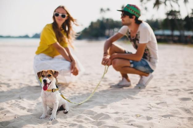 Junges stilvolles hipster-paar in der liebe, das das spielen des hundewelpen jack russell im tropischen strand, im weißen sand, im kühlen outfit, in der romantischen stimmung spielt, spaß, sonnig, mann frau zusammen, urlaub